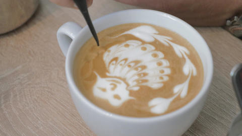 On the table is a cup of coffee with foam and the man draws on the foam pattern Footage