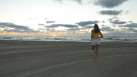 Young woman running on the beach towards sea at sunrise Footage
