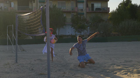 Couple playing volleyball and having fun on the beach Footage