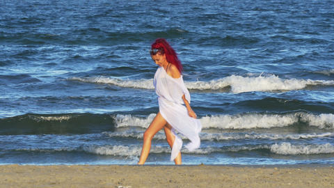 Young beautiful girl walking on the beach by the sea and playing with her feet i Footage