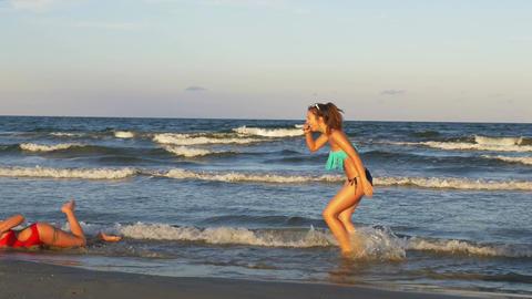 Young beautiful women enjoying teasing one another on a beautiful wet sandy beac Footage