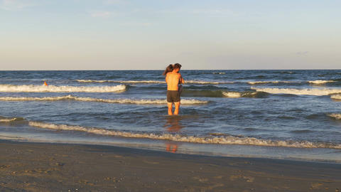 Romantic couple playing and teasing one another in the sea Footage