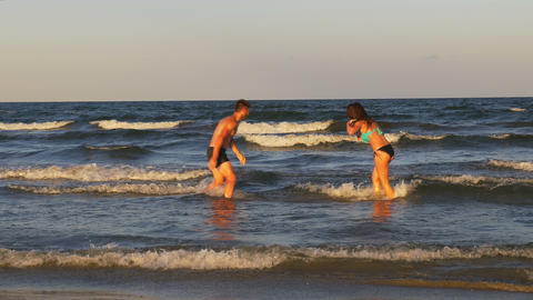 Beautiful romantic young couple teasing one another and playing in the sea Footage