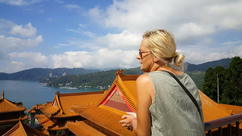 European blonde woman looking at the lake over the rooftops of Wenwu temple Footage