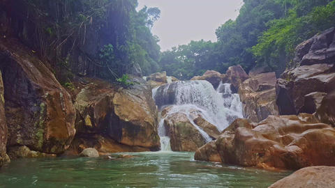 Stormy Waterfall between Rocks Falls into Pond in Tropics Footage