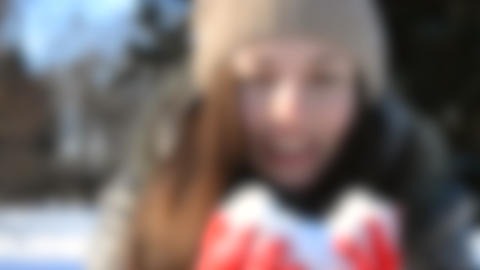 Blurred background. Girl blows snow with hands. Beautiful Girl Live Action