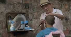 Senior street Barber cuts a man with a straight razor, while a man looks in the  Live Action
