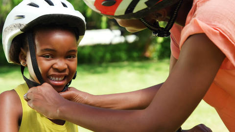 Woman putting a cycling helmet to his daughter Live Action