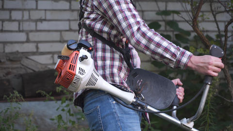 Man with electric lawnmower, lawn mowing. Gardener trimming garden. Suburb Live Action