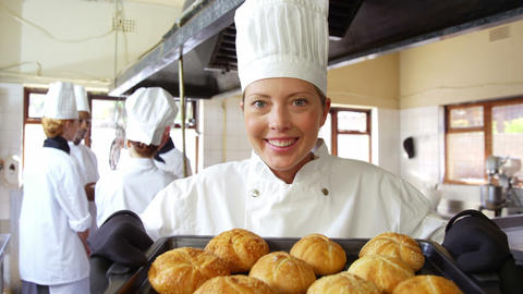 Female chef holding bun in cooling tray Footage