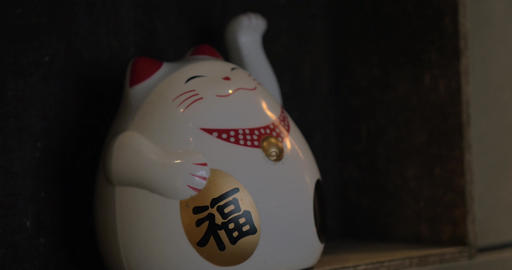 Fortune cat figurine beckoning with paw Footage