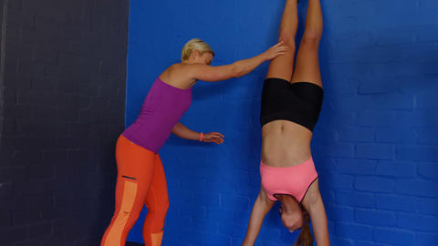 Fitness trainer assisting woman to perform handstand Live Action