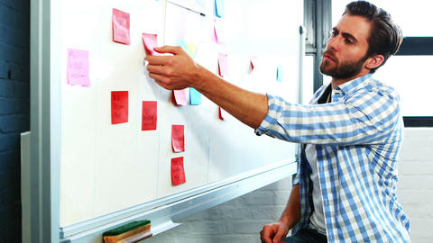 Man putting sticky notes on whiteboard Live Action