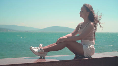 A girl in white shorts and a T-shirt walks along the city promenade. A girl sits Live Action