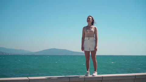 A girl in white shorts and a T-shirt along the city promenade. A girl walks Live Action