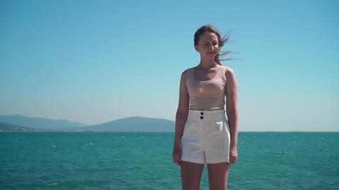 By the sea is a girl in white shorts and a T-shirt. A girl stands on the Live Action