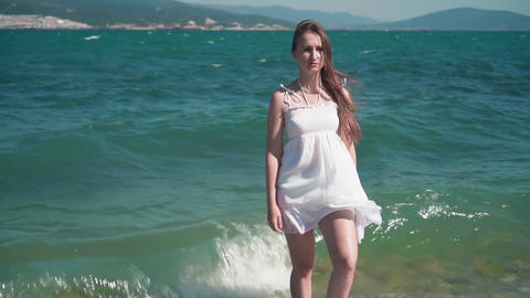 A girl in a white beach dress, stands along the seashore. A beautiful girl with Live Action