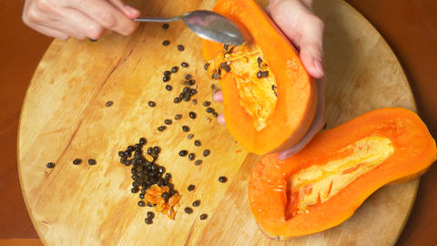 exotic fruits on the table. 4k, women's hands prepare papaya for a cutting board Live Action