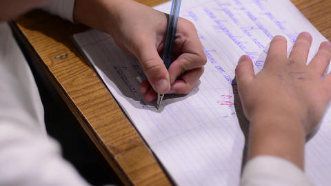 A school-age child writes in a notebook. The child writes with his left hand Live Action