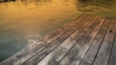 Ripples waves on lake & wood piers,sun light reflection in water at dusk Footage