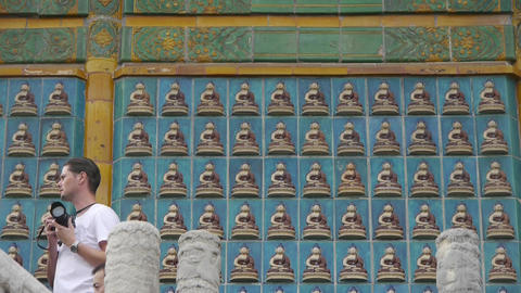 tourist photography & ancient east buddha totem wall Stock Video Footage