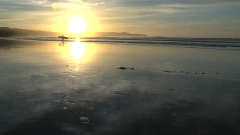 surfer walking on the beach ready for a morning surf Stock Video Footage
