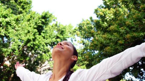 Beautiful woman raising arms and enjoying outdoors Live Action