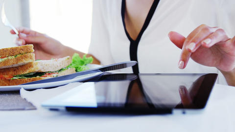 Woman eating lunch and using tablet computer Live Action