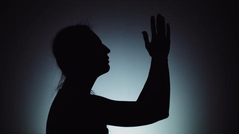 A woman prays to God, folding his arms and stretching them up. Emotions, prayer Live Action