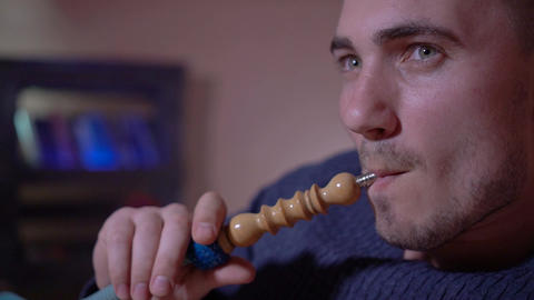 A young guy smokes a hookah, exhales smoke Live Action