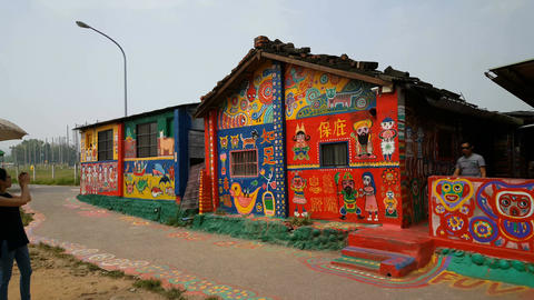 Woman takes pictures of gallery Rainbow Village Footage