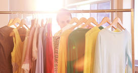 Woman selecting clothes from clothing rack Live Action
