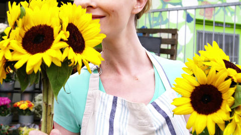 Beautiful female florist smelling bunch of sunflower Footage