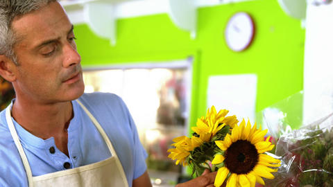 Male florist arranging flower bouquet in flower shop Footage