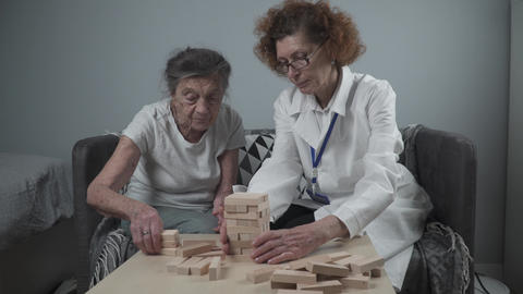 Senior woman practice skills build wooden blocks, building tower and trying not Live Action