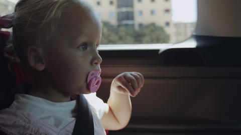 Little girl with soother having a car journey Live Action