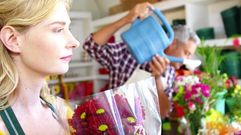 Beautiful female florist smelling bouquet of flower Footage