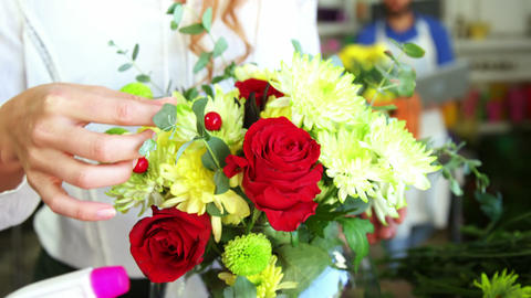 Female florist arraigning flower in flower vase Footage