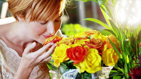Beautiful female florist smelling roses Footage