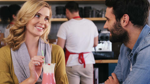 Couple interacting while having a cup of coffee and milkshake Live Action