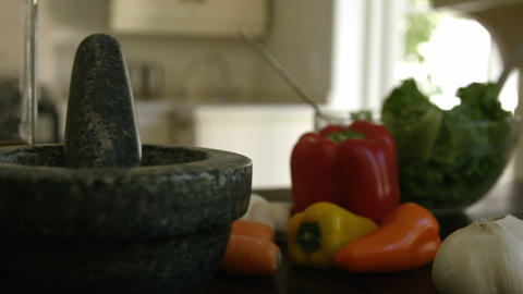 Mortar,pestle and vegetables on kitchen worktop Live Action
