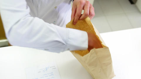 Pharmacists packing medicine in paper bag Live Action
