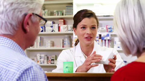 Pharmacist assisting the bottle of drug to customers Live Action