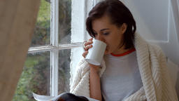Woman reading magazine while having cup of coffee Live Action