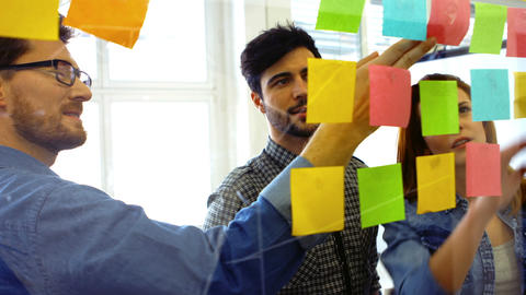 Business executives discussing over sticky notes Live Action