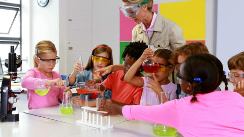 School teacher assisting school kids in chemical experiment in laboratory Footage