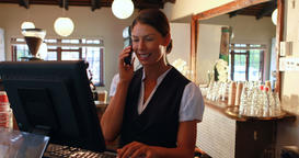 Waitress talking on the phone at counter Live Action