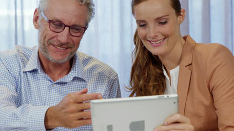 Businesswoman and coworker discussing over digital tablet Live Action