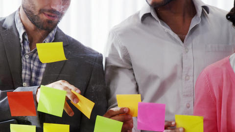 Businesspeople interacting over sticky notes Live Action