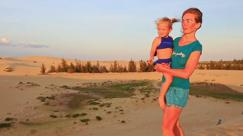 Closeup Mother Carries in Arm Small Girl against Dunes at Sunset Footage